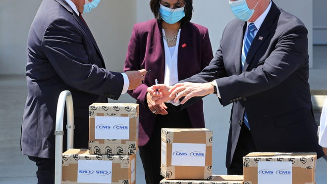Vice President Mike Pence signs PPE packages of personal protective equipment with Florida governor Ron DeSantis, left, and Seema Verma, U.S. Centers for Medicare & Medicaid Services adminisitrator, that were being delivered to the Westminster Baldwin Park retirement community, in Orlando, Fla., Wednesday, May 20, 2020. With rising COVID-19 cases nationally, shortages in protective gear are beginning to reappear.