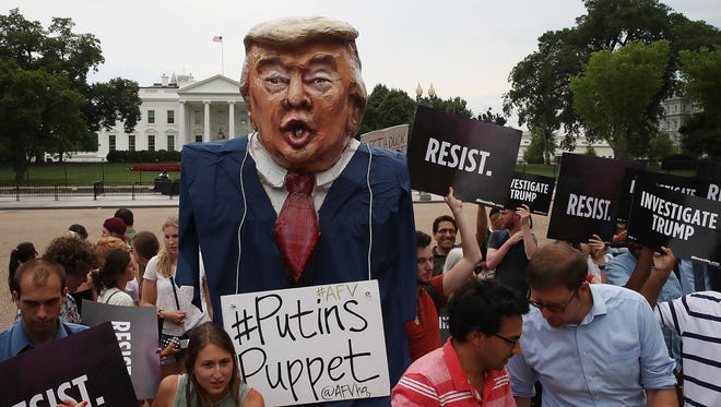 WASHINGTON, DC - JULY 11:  People protest against U.S. President Donald Trump in front of the White House on July 11, 2017 in Washington, DC. The group Moveon.org organized the protest against the president for his campaign's alleged contact with representatives from Russia during the 2016 presidential election.