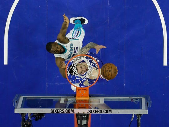 Philadelphia 76ers' JJ Redick, bottom, goes up to shoot past Charlotte Hornets' Kemba Walker during the first half of an NBA basketball game, Monday, March 19, 2018, in Philadelphia.