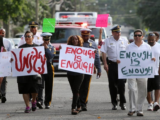 Community members, police officers and firefighters participate in the peace march Thursday through Plainfield.