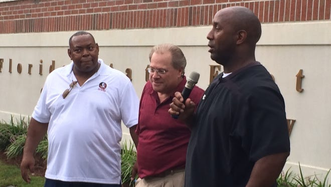 Former FSU players and Hall of Fame inductees Aaron Carter (left) and Amp Lee meet with fans at the program's Sod Cemetery prior to Saturday's game. Tallahassee Doug Mannheimer (middle) came up with the new tradition.