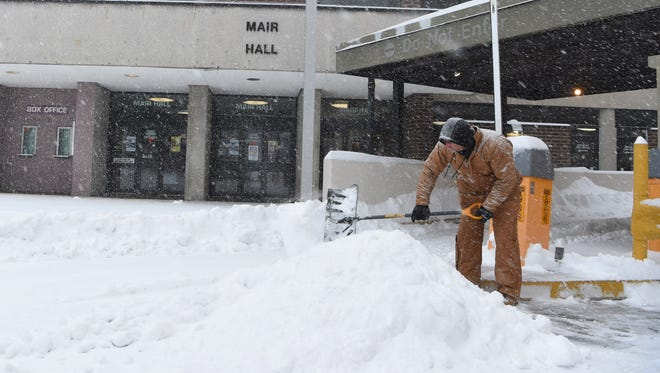 John Card, an employee at the Poughkeepsie Grand Hotel, shovels the entrance and exit to the hotel's parking garage in the City of Poughkeepsie.