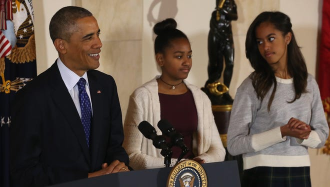 """President Obama speaks as his daughters, Sasha, left, and Malia, look on before pardoning """"Cheese"""" and his alternate, Mac -- both 20-week-old, 48-pound turkeys, during a ceremony at  the White House on Nov. 26."""
