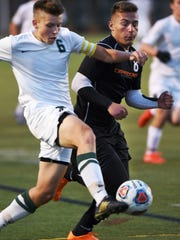Novi's Eric Rice (left) takes control the the ball in front of Dearborn's Abraham Ouza.