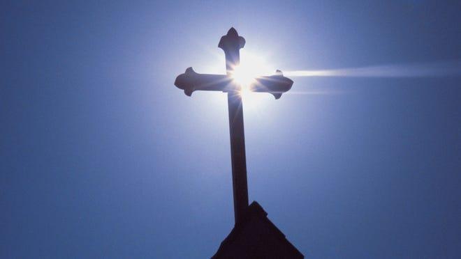 Sunlight on cross above a church