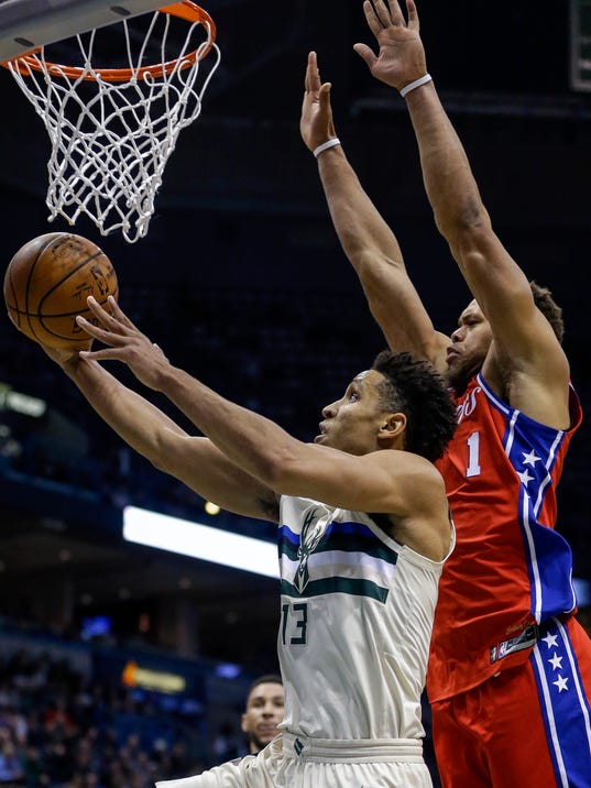 Milwaukee Bucks' Malcolm Brogdon, left, puts up a reverse layup as Philadelphia 76ers' Justin Anderson tries to defend during the second half of an NBA basketball game Monday, Jan. 29, 2018, in Milwaukee. (AP Photo/Tom Lynn)