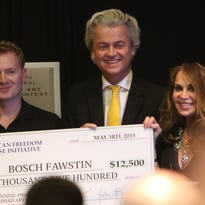 Artist Bosh Fawstin, left, is presented with a check for $12,500 by Dutch politician Geert Wilders, center, and Pamela Geller, right, during the American Freedom Defense Initiative program at the Curtis Culwell Center on May 3, 2015, in Garland, Texas.
