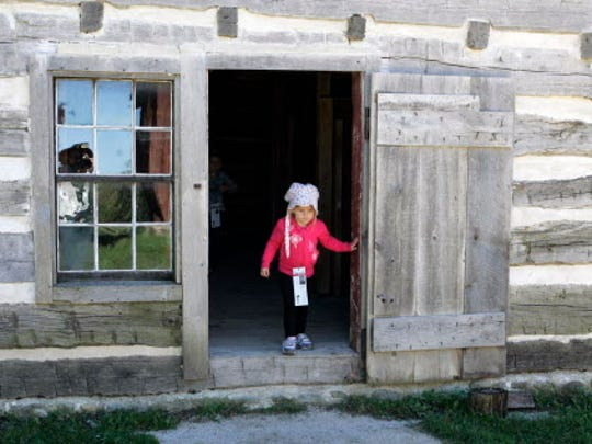 Katherine Jeffers, 3, of Wheaton, Ill. steps out of a shed on the Schottler farm in the German area at Old World Wisconsin during Autumn on the Farms.