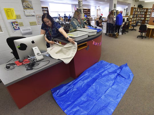 Librarian Bridget Bowers, left, and study hall supervisor Joanne Surfus demonstrate what is required to cover equipment and desks inside an area of the Sevastopol School library. The library addition was built in 1965 and has been leaking for at least 15 years.