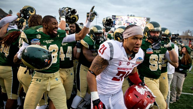 Washington State linebacker Eric Oertel (21) leaves the field as Colorado State players celebrate their last-second victory Saturday in the New Mexico Bowl.