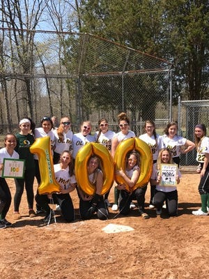 The Our Lady of Mercy softball team celebrates Morgan Hagerty's 100th career hit last weekend.
