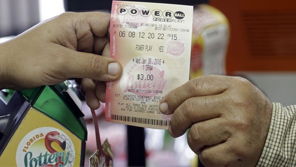 A clerk hands over a Powerball ticket to a customer