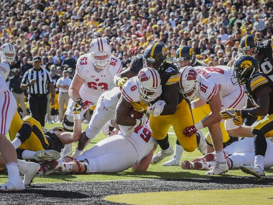 Wisconsin running back Corey Clement pushes past Iowa tackle Jaleel Johnson and into the end zone Saturday at Kinnick Stadium in Iowa City.