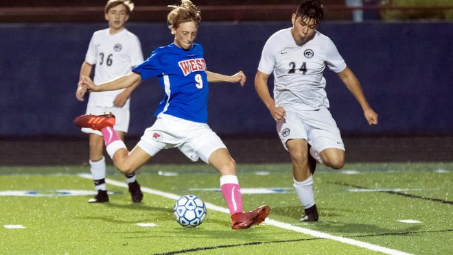 Woody Green (9) of West Henderson attempts a goal for the Falcons against the North Buncombe Blackhawks in last year's match at Johnson Field.