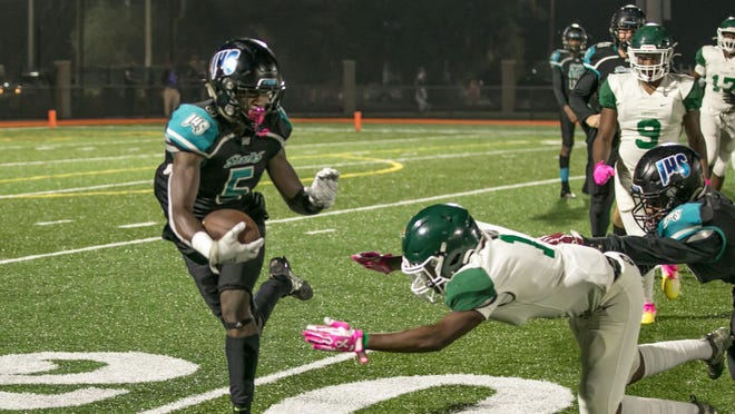 Islands High's Shamar Sandgren (5) evades the grasp of Windsor Forest's Jamario Blige during a game in 2019 at Memorial Stadium. The 2020 season will start the first week of September, with the Friday night action on Sept. 4.
