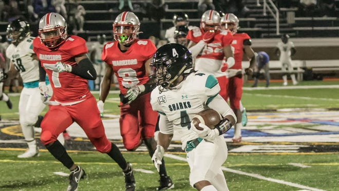 Islands senior running back Donavan Davelaar (4) cuts upfield while being chased by Jenkins High's Rayqwon Allen (7) and Tony Edwards Jr. (3) on Friday at Memorial Stadium.