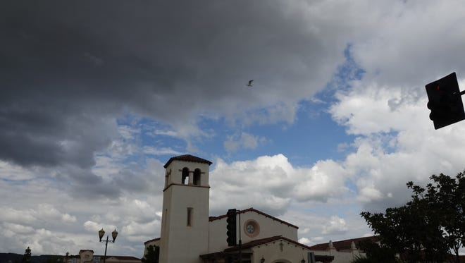 Both dark and puffy white clouds crowded against patches of blue sky over Old Town Camarillo Sunday afternoon. Weekend showers had mostly ended by Sunday morning, but more rain is set to blow in this week.