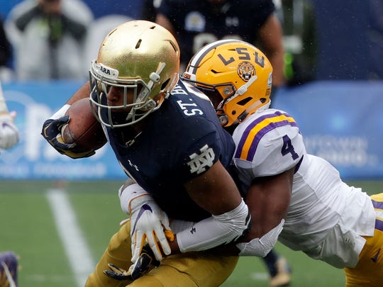 Notre Dame wide receiver Equanimeous St. Brown, left, is stopped after a reception by LSU linebacker K'Lavon Chaisson (4) during the first half of the Citrus Bowl NCAA college football game, Monday, Jan. 1, 2018, in Orlando, Fla. (AP Photo/John Raoux)