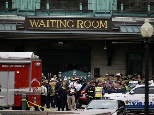 Emergency officials stand outside of the Hoboken Terminal