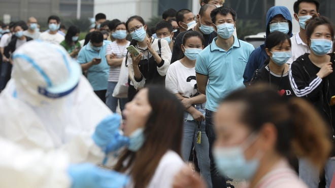 People line up May 15 for coronavirus testing at a large factory in Wuhan in central China's Hubei province. In June, China reported using batch testing as part of a recent campaign to test all 11 million residents of Wuhan, the city where the virus first emerged in late 2019.