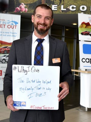 "Billy Hammill holds a sign explaining why he gives to United Way of the Mid-Willamette Valley. ""The United Way helped my family. That is why I give!!"" the sign reads. United Way took photos of their donors explaining their giving motivations to promote #GivingTuesday."