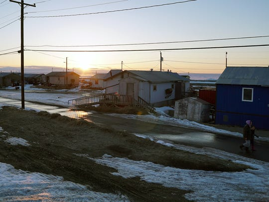 The sun sits low on the western horizon above Shishmaref