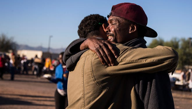 Tyrelle Jackson (left), who is homeless, hugs volunteer Carlos Beauchamp before the Society of St. Vincent de Paul in Phoenix served a Thanksgiving Day meal.