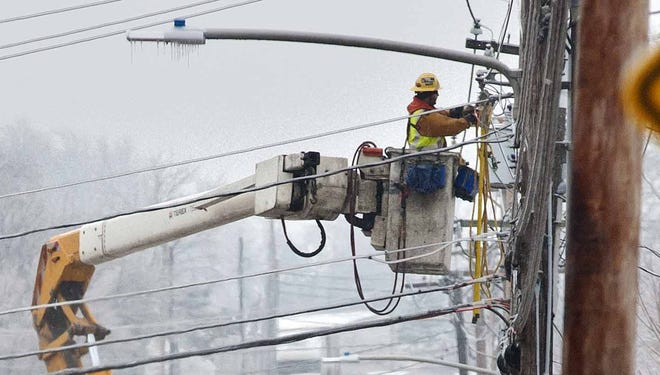 Utility crews respond to a downed power line at an intersection in South Burlington, Vt., on Monday.