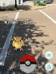 An iPhone screenshot shows the Pokemon Pidgey in augmented reality at the corner of East Baltimore Street and South Liberty Street in downtown Jackson on Wednesday, July 13.