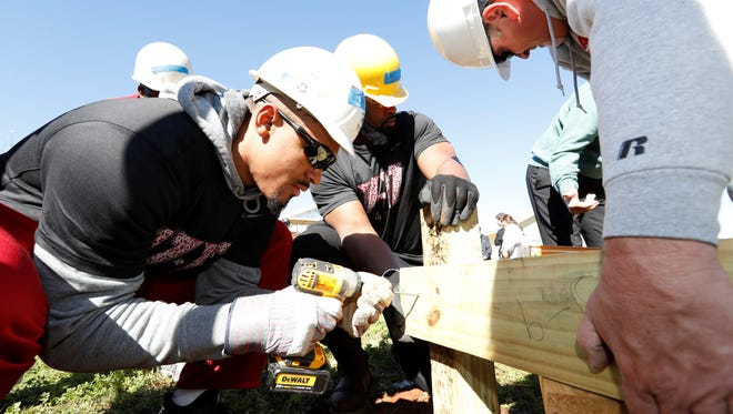 Alabama football team members Jalen Hurts and Isaiah Buggs works with Habitat for Humanity on the 17th championship house build.