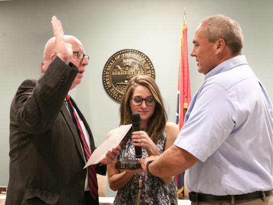 Robertson County Mayor Howard Bradley administers the oath of office to Jeff White while junior board member Emma Friedmann assists.