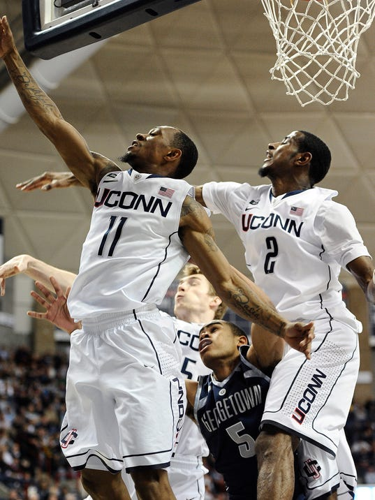 FILE - In this Feb. 27, 2013, file photo, Georgetown's Markel Starks, center, is caught between Connecticut's Ryan Boatright, left, Niels Giffey, rear center, and DeAndre Daniels, right, after Boatright blocked Starks' shot attempt during an NCAA college basketball game in Storrs, Conn. The university announced Friday, April 25, 2014, that Daniels has filed the necessary paperwork with the NBA and will forgo his senior season of eligibility. The school says guard Boatright will return next season. (AP Photo/Jessica Hill, File)