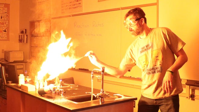 Dr. Dan Casmier, chemistry instructor at Great Falls College MSU, performs a Science at the College experiment showing the flammability of club moss.
