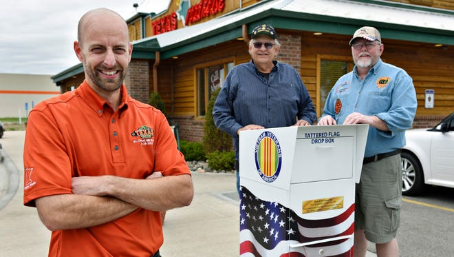 Shaun Mason, owner of Texas Roadhouse, Waite Park, with Bob Behrens and James Kowitz of the Vietnam Veterans of Central Minnesota Chapter 290, show the recently installed tattered flag donation box Saturday outside the restaurant.