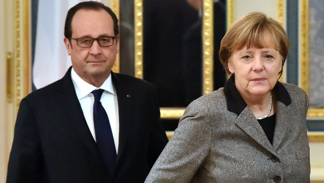 French President Francois Hollande and German Chancellor Angela Merkel walk to their meeting with the Ukrainian President in Kiev on Feb. 5, 2015.