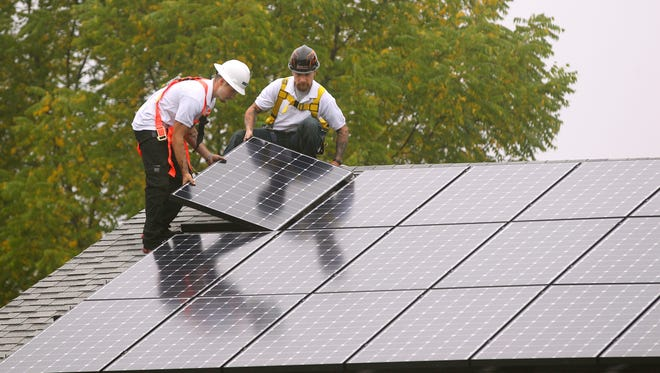 Zak Richards, left, and Doug Vordran of Renewable Rochester install solar panels at a residence in Ogden.