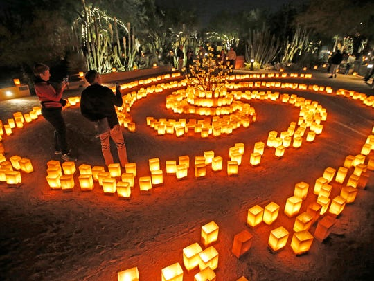 Visitors walk through the spinal of luminarias during