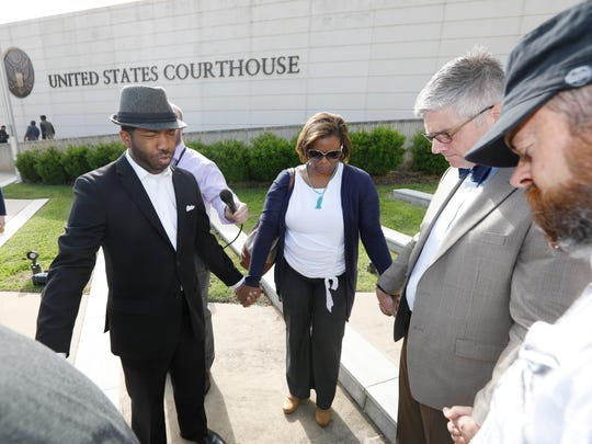In this April 9 2018 file photo, Rev. C.J. Rhodes, pastor of Mt. Helm Baptist Church in Jackson, and a member of Clergy for Prison Reform, second from left, leads a prayer vigil with area clergy, following a news conference on the steps of the federal courthouse in Jackson.