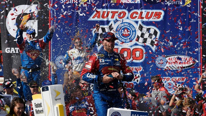 Jimmie Johnson celebrates his win Sunday at the Auto Club 400 at Auto Club Speedway.