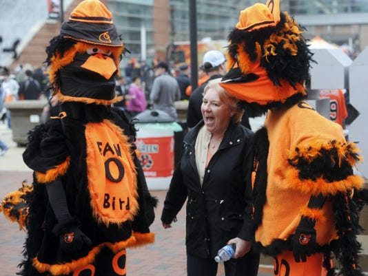Janet Stevens of Baltimore, poses with a couple of dressed up Orioles fans before the home opener at Camden Yards on Friday.