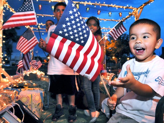 Jacob Lopez, 3, is handed an American Flag while riding in the Lopez Glass float on during the city's 2014 Electric Light Parade. In addition to the parade, Friday downtown events this year will include a race and the monthly art Ramble through Main Street shops and galleries.