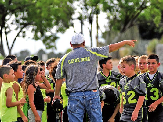 Jaime Guzman for the Sun-News      Members of the Gator Football Organization listen as one of the coaches gives instructions during their practice on Friday afternoon.