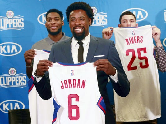Los Angeles Clippers DeAndre Jordan, middle, the league rebounding champion, is reintroduced at a Staples Center news conference with teammates, forward Branden Dawson, left, and guard Austin Rivers, right, in Los Angeles on Tuesday. The Clippers managed to keep Jordan after he changed his mind about his verbal commitment to Dallas. Jordan thought the Dallas Mavericks offered everything he wanted, including a fresh start and a bigger offensive role. When Jordan thought about it a little more, the craziest free-agent recruitment story in recent NBA history ended with him back on the Los Angeles Clippers.