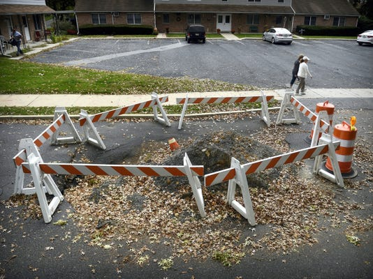 Barricades surround a sinkhole this week in the 900 block of East Maple Street in Palmyra. The road has been closed to through traffic since June.