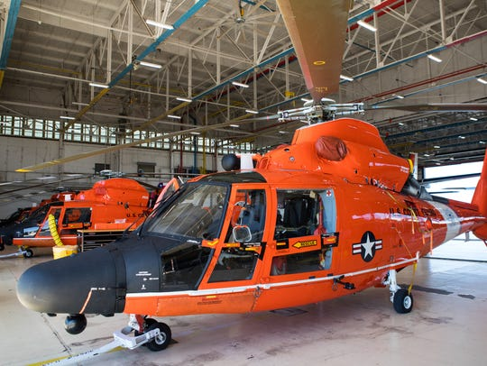 Coast Guard helicopters sit in a hangar at the Coast