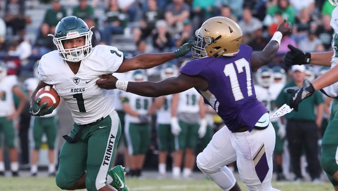 Trinity's Rondale Moore (1) eludes Male's Dallas Douglas (17) on his way to a 23 yard touchdown run at Male High School.Sep. 8, 2017