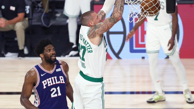 Celtics center Daniel Theis, right, dunks past Philadelphia 76ers center Joel Embiid on Aug. 23. Theis, Robert Williams and Enes Kanter have all contributed at the center position during Boston's playoff run, so far.