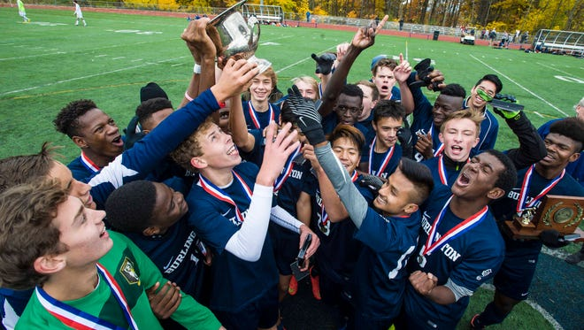 Burlington players celebrate their victory over Essex after the Division 1 state boys soccer championship game in Burlington on Saturday, November 5, 2016.
