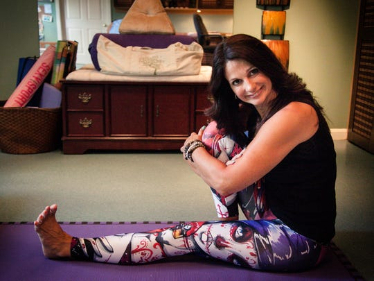 Roberta Brummel, a certified yoga teacher, stretches on a yoga mat in her home in West Cornwall Township.