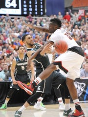 MSU's Denzel Valentine passes to an open Travis Trice past Louisville's Chinanu Onauku Sunday, as teammate Bryn Forbes looks on. Forbes and Valentine won two state titles together at Lansing Sexton High School. Valentine scored 15 points, Forbes 14 in Sunday's Elite Eight win.